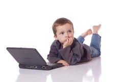 Muchacho lindo con un ordenador portátil Imagen de archivo