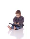 Muchacho lindo con un ordenador portátil Imagen de archivo libre de regalías