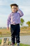 Niño pequeño lindo que se coloca en una roca Fotografía de archivo