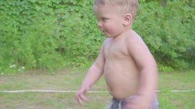 Niño pequeño lindo que se divierte afuera con la regadera del agua en jardín del verano Cámara lenta almacen de video