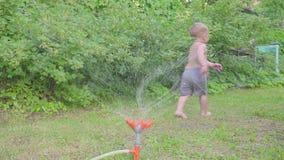 Niño pequeño lindo que se divierte afuera con la regadera del agua en jardín del verano Cámara lenta metrajes
