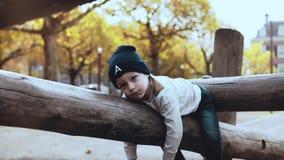 Niño pequeño lindo que se divierte en parque de la aventura El niño nervioso confuso en sombrero que vacila, pegado en cuerdas cu almacen de metraje de vídeo