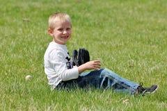 Niño pequeño lindo que se sienta en la hierba con su guante de béisbol Imágenes de archivo libres de regalías