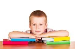 Niño pequeño lindo que se sienta en la tabla con los libros en blanco Fotografía de archivo