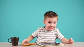 Niño pequeño lindo que se sienta en la tabla y que juega en la tableta El niño está bebiendo té almacen de video