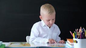Niño pequeño lindo que se sienta en la tabla y la lectura Ni?o de la escuela primaria Concepto de la educaci?n De nuevo a escuela almacen de metraje de vídeo