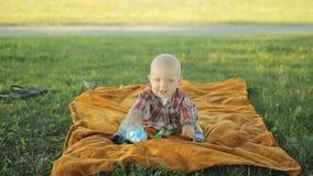 Niño pequeño lindo que se sienta en una manta en el parque El bebé menos que un año y él jugó almacen de video