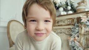 Niño pequeño lindo que sonríe a la derecha en la cámara almacen de video
