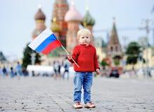 Niño pequeño lindo que sostiene la bandera rusa Fotos de archivo
