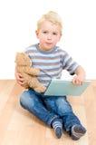Niño pequeño lindo que sostiene su oso y libro de peluche aislados Imagen de archivo
