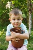 Niño pequeño lindo que sostiene un pote de arcilla viejo Jarro de leche imagen de archivo