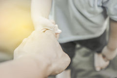 Niño pequeño lindo que tira del mano-finger del ` s del papá a disposición Foto de archivo libre de regalías