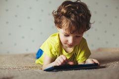 Niño pequeño lindo que usa un cojín Niño que juega con la tableta digital que miente en una cama Reclinación - Cofee de consumici imagenes de archivo
