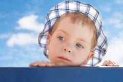 Niño pequeño lindo triste en sombrero en fondo del cielo Imágenes de archivo libres de regalías