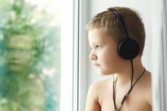 Niño pequeño loking en ventana Fotos de archivo