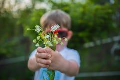 Niño pequeño no en el foco que sostiene los flovers que presentan las flores Foto de archivo libre de regalías