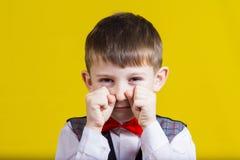 Niño pequeño obstinado, triste, trastornado, niño aislado sobre backg amarillo imagen de archivo