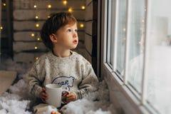 Niño pequeño para Papá Noel que espera Niño pequeño rizado lindo que se sienta cerca de la ventana fotos de archivo