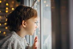 Niño pequeño para Papá Noel que espera Niño pequeño rizado lindo que se sienta cerca de la ventana foto de archivo libre de regalías