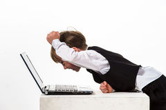 Niño pequeño pecoso del rojo-pelo con el ordenador portátil. Fotos de archivo