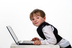 Niño pequeño pecoso del rojo-pelo con el ordenador portátil. Imagenes de archivo