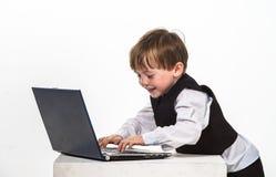 Niño pequeño pecoso del rojo-pelo con el ordenador portátil. Fotos de archivo libres de regalías