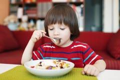 Niño pequeño pensativo con la ensalada de fruta Fotos de archivo libres de regalías