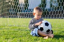 Niño pequeño pensativo con un fútbol Imágenes de archivo libres de regalías