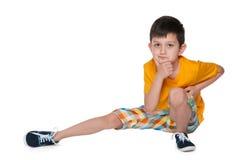 Niño pequeño pensativo en una camisa amarilla Imágenes de archivo libres de regalías