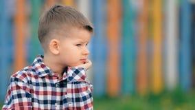 Niño pequeño pensativo que se sienta afuera en un fondo colorido almacen de metraje de vídeo