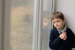Niño pequeño pensativo triste que mira a través de la ventana Fotos de archivo