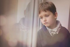 Niño pequeño pensativo triste que mira a través de la ventana Foto de archivo libre de regalías