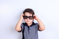 Niño pequeño precioso en gafas de sol, lanzamiento del estudio en blanco Niños fotos de archivo libres de regalías