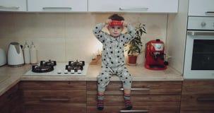 Niño pequeño precioso en la cocina que juega con una verdura Epopeya roja 4K almacen de video