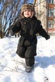 Niño pequeño precioso en los monos de nieve negros que corren en invierno Imagenes de archivo