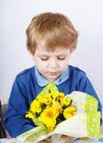 Niño pequeño precioso lindo de 3 años que huele las flores amarillas para m Fotos de archivo