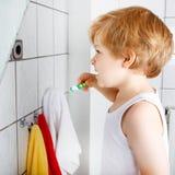 Niño pequeño precioso que cepilla sus dientes, dentro Imagen de archivo