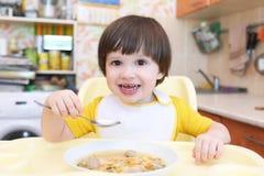 Niño pequeño precioso que come la sopa con la cocina de las bolas de carne en casa Imágenes de archivo libres de regalías