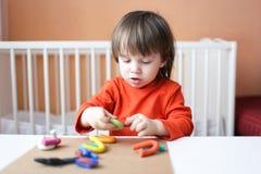 Niño pequeño precioso que juega con plasticine en casa Fotografía de archivo