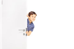 Niño pequeño precioso que se escabulle una ojeada detrás de una puerta foto de archivo libre de regalías