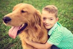 Niño pequeño que abraza su perro casero del golden retriever Imagen de archivo
