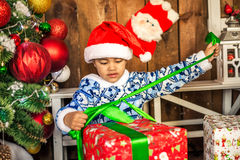 Niño pequeño que abre un regalo de Navidad Imagen de archivo