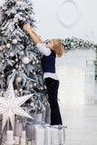 Niño pequeño que adorna el árbol de navidad El concepto de Christm Fotografía de archivo libre de regalías