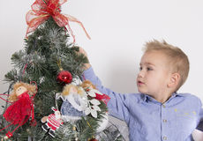 Niño pequeño que adorna un árbol de navidad Imágenes de archivo libres de regalías
