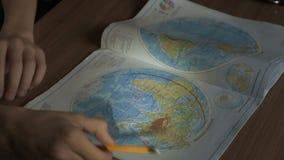 Niño pequeño que aprende la geografía - mirada de los mapas y del globo almacen de metraje de vídeo