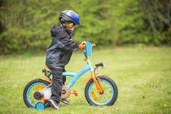 Niño pequeño que aprende montar la primera bici Imagenes de archivo