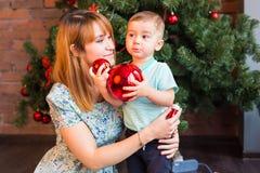 Niño pequeño que ayuda a su mamá a adornar el árbol de navidad Imagenes de archivo