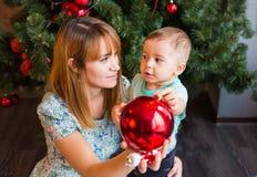 Niño pequeño que ayuda a su mamá a adornar el árbol de navidad Foto de archivo libre de regalías