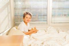 Niño pequeño que bebe el zumo de naranja que se sienta en cama Fotografía de archivo