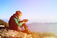Niño pequeño que camina en las montañas escénicas que miran el cono del pino Foto de archivo libre de regalías